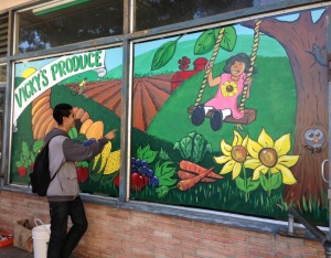 A youth admires the new mural he helped paint in front of Vicky's Produce to help better market healthy foods to customers. Source: https://www.facebook.com/Jovenessanoswatsonville
