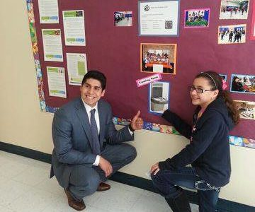 Praxina and city council member Rey Saldaña pose by a photo of the hydration station they would like to see installed at Five Palms. (Photo Source: Cathy Lopez)