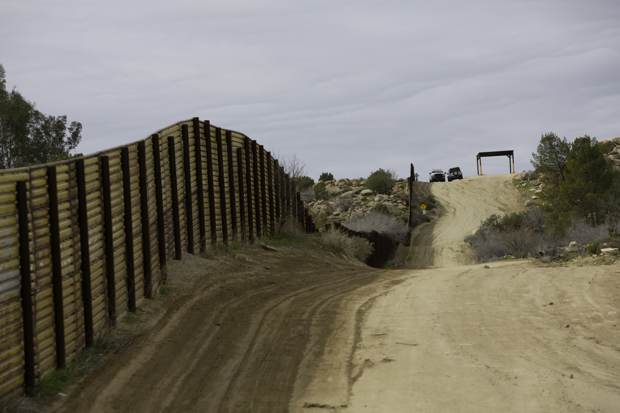 Border Patrol Vehicles Near Barrier Wall in California moral disengagement