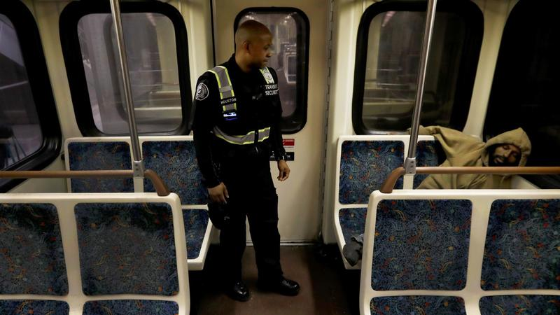 A Metro transit security guard wakes up a sleeping person on the Red Line. (Francine Orr / Los Angeles Times)