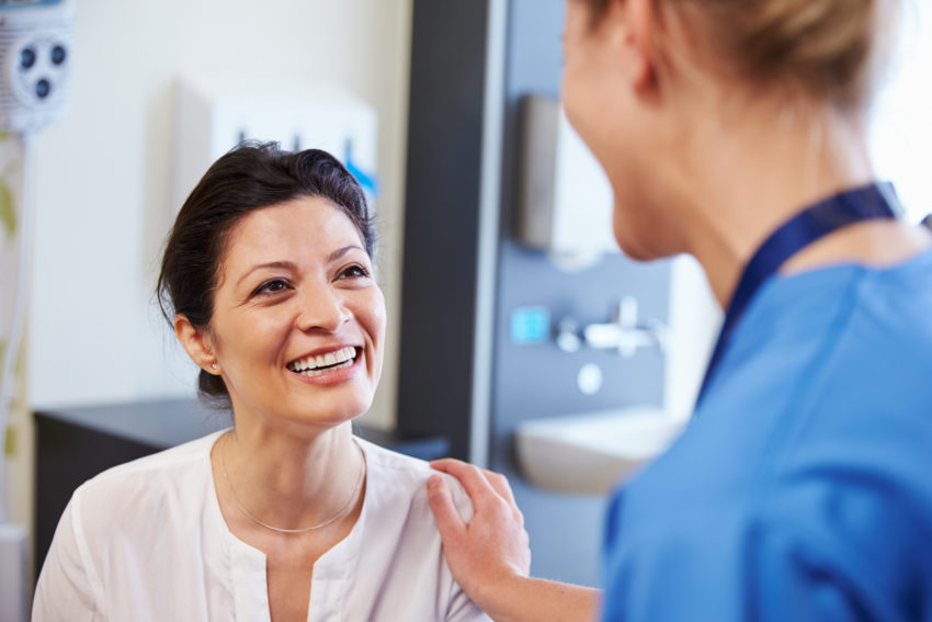 Latino cancer patient smiling with doctor nurse clinic