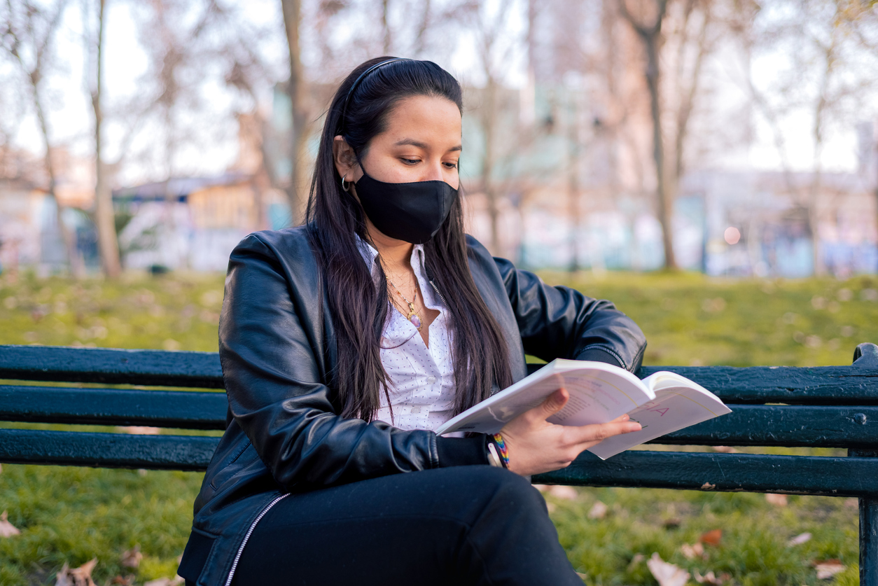 latina reading in park bench with face mask to prevent covid-19 coronavirus